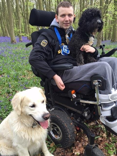 boy in electric wheelchair with 2 dogs