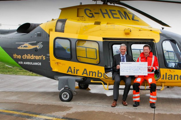 Air ambulance helicopter and two men holding a donation cheque
